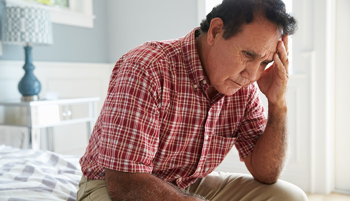 Man Sitting On Bed Suffering With Depression