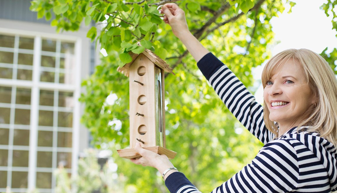 A woman smiles as she fills a bird house in a yard.
