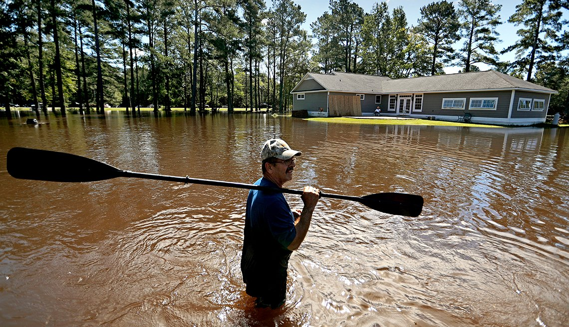 The home of Kenny Babb is surrounded by water as he retrieves a paddle that floated away while the Little River continues to rise in the aftermath of Hurricane Florence in Linden, N.C., Tuesday, Sept. 18, 2018