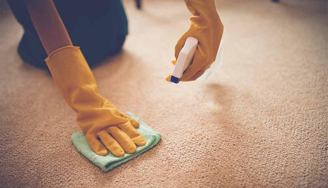 Errores que cometemos al limpiar y cómo evitarlos - Persona limpiando una alfombra
