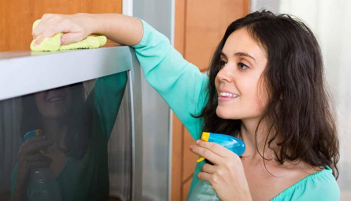 Errores que cometemos al limpiar y cómo evitarlos - Mujer con un spray en la mano limpiando un televisor