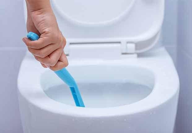 Errores que cometemos al limpiar y cómo evitarlos - Persona limpia un baño sin guantes