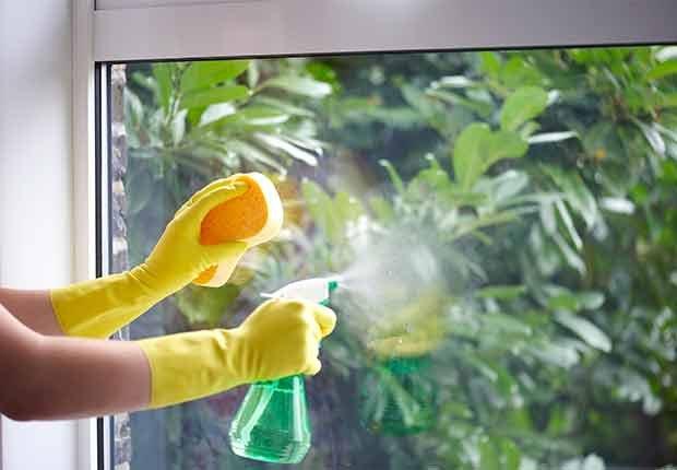 Errores que cometemos al limpiar y cómo evitarlos - Persona limpiando una ventana