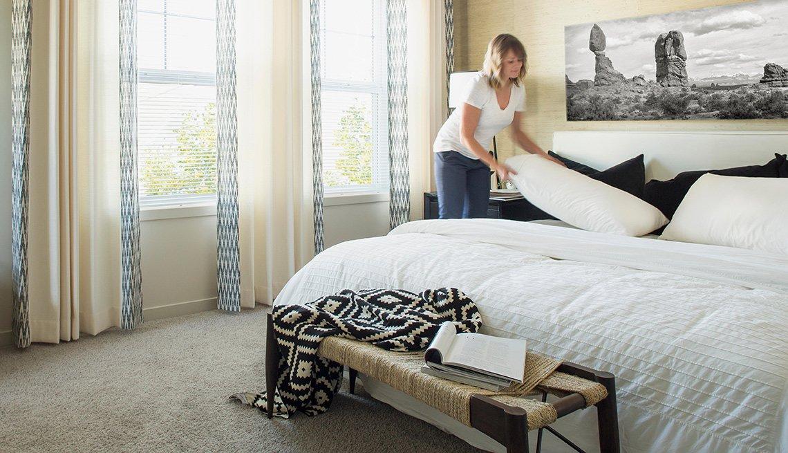 Una mujer tiende la cama de la casa