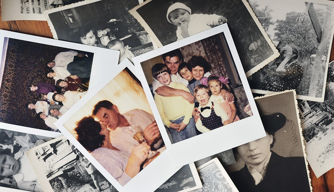 Pile of family photographs on table, overhead view