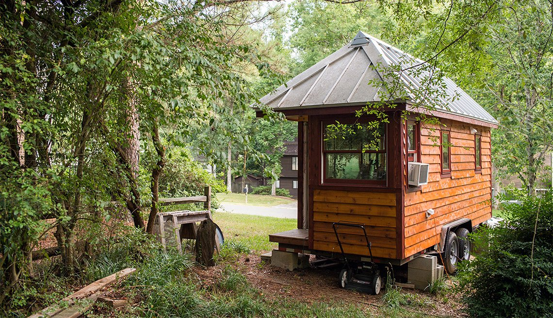 A tiny home on wheels in a wooded area