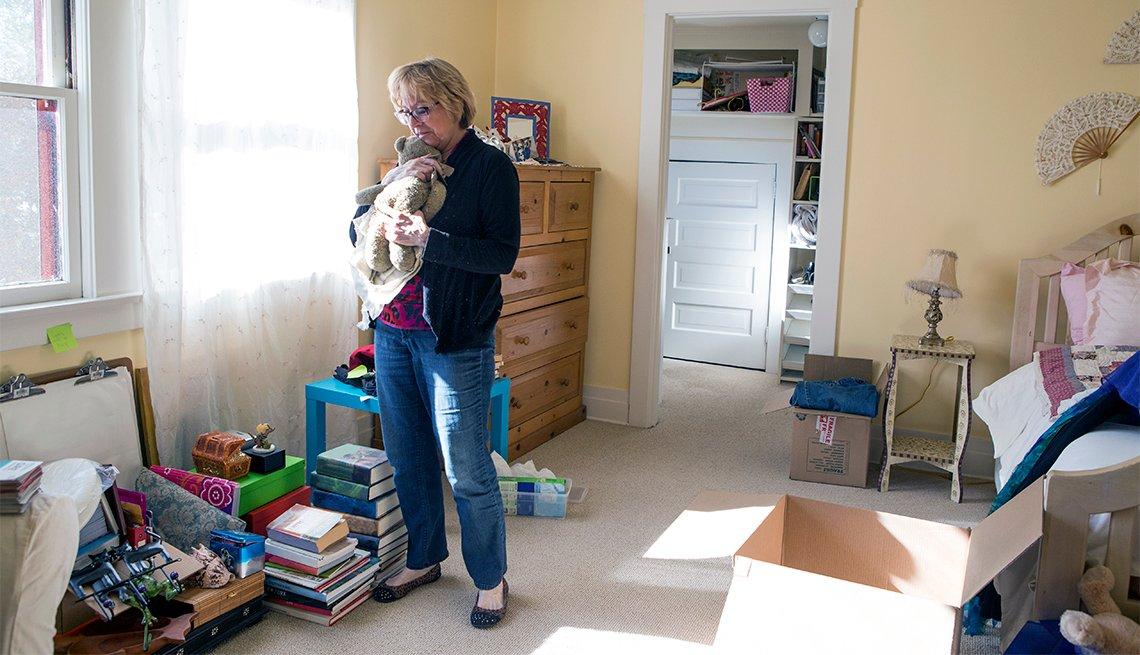Mujer de mediana edad abraza un oso de peluche en la habitación de sus hijas