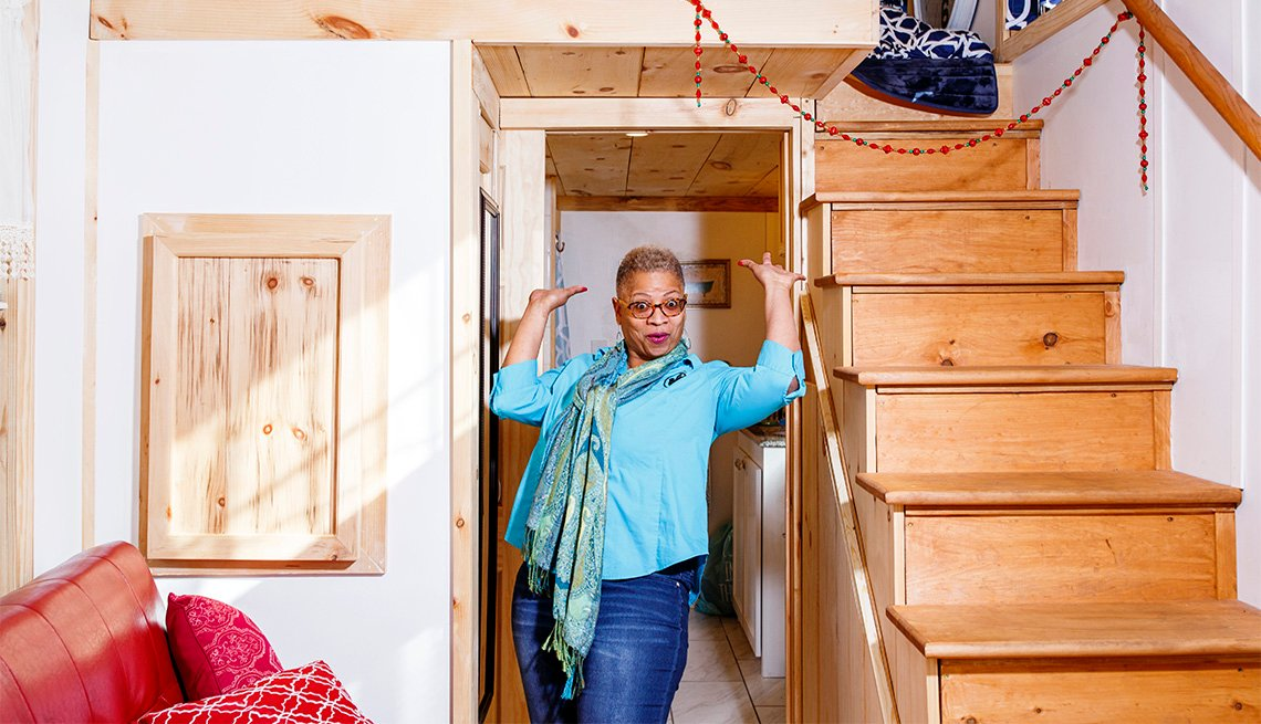 A woman standing in the living space of her tiny home proudly raises her hands.
