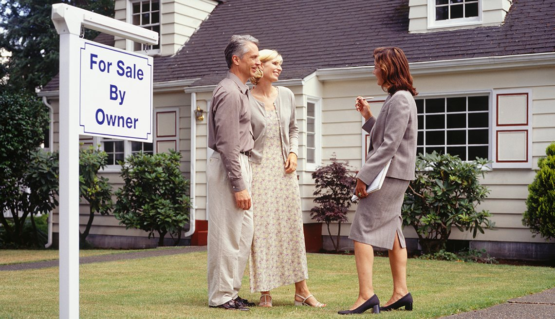 Couple talking to real estate agent on front lawn, sign in yard reads for sale by owner