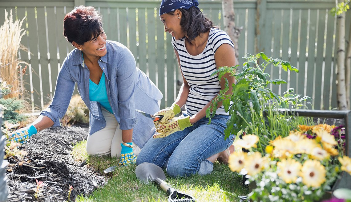 Two women knelling in a garden with garden tools in their hand.