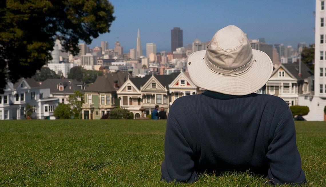 Un hombre acostado en un parque, con vista a la ciudad de San Francisco.