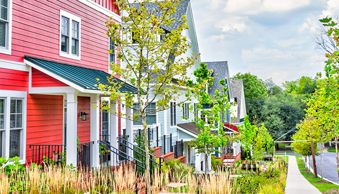 Colorful multicolored red, blue painted residential new townhouses, homes, houses in Maryland with cars on street.