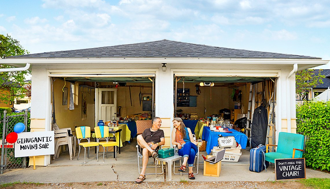 A man and a woman sit in front of an open garage with items for sale. Signs read gihugantic moving sale and don't miss this vintage chair!