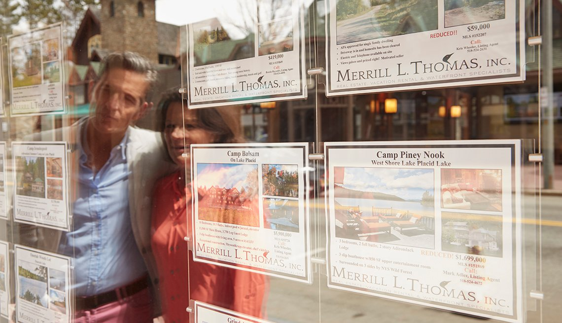 A man and woman looking at housing ads posted on a window.