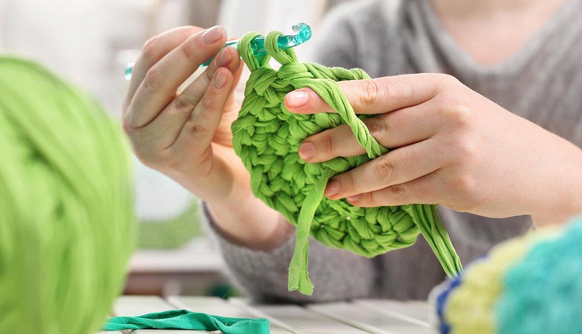 Una mujer teje al estilo crochet con lana de color verde.
