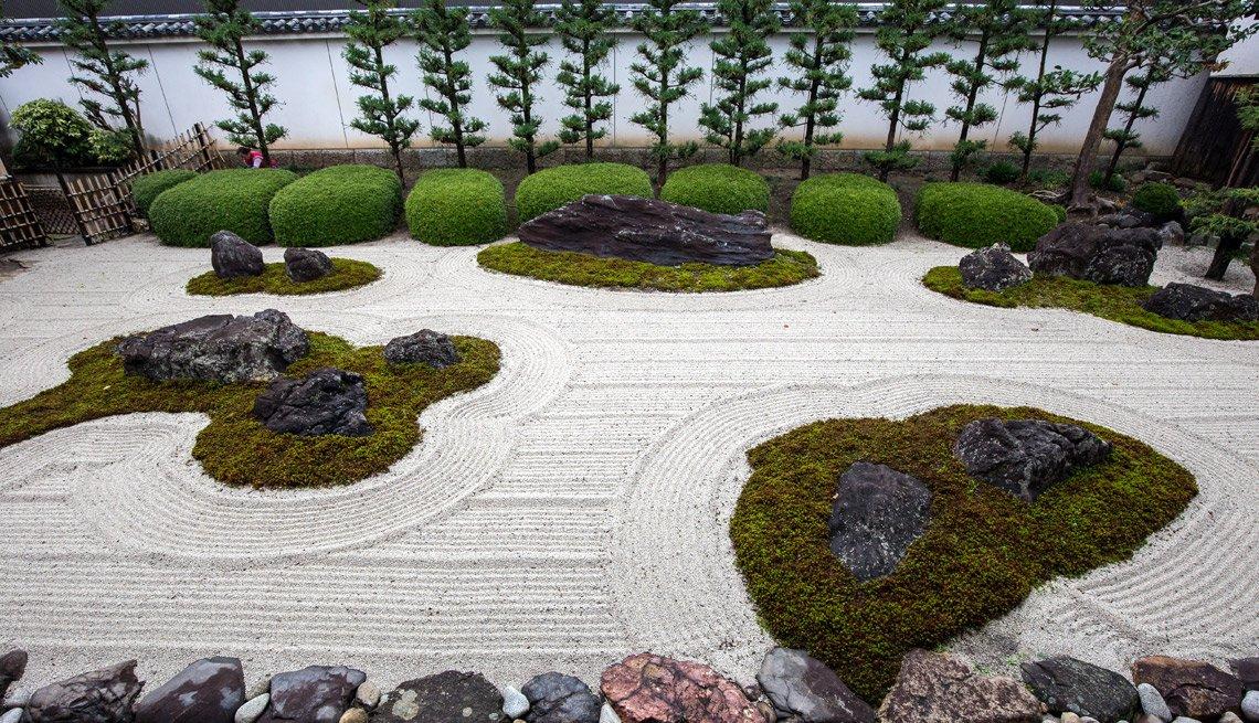 Jardín zen con rocas, musgo y árboles.