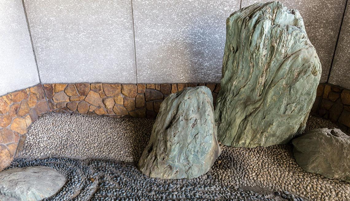 Jardín zen hecho con rocas en el rincón exterior de una casa.