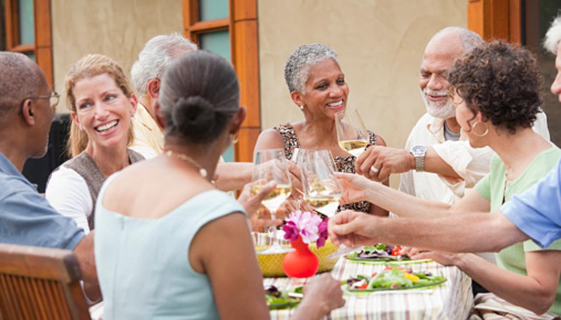 Grupo de adultos mayores cenando en la mesa.