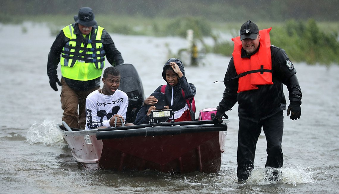 Three children in a boat are rescued by volunteers during Hurricane Florence