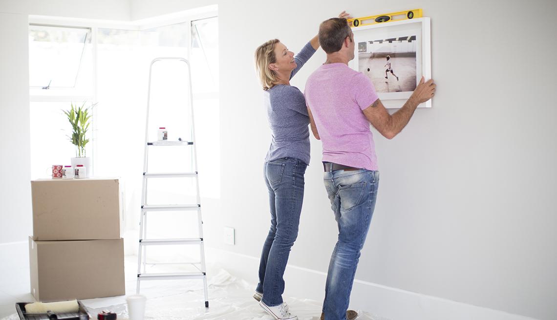 Pareja cuelga un cuadro en una pared de su casa.