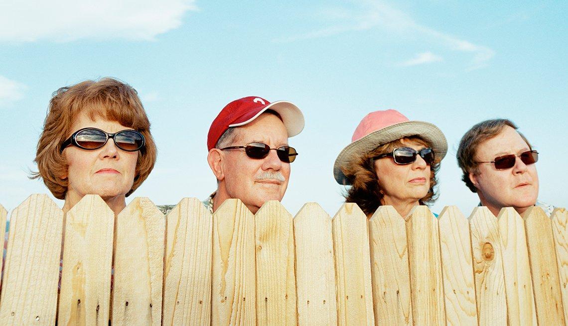 Un grupo de vecinos observa por encima de una cerca de madera.
