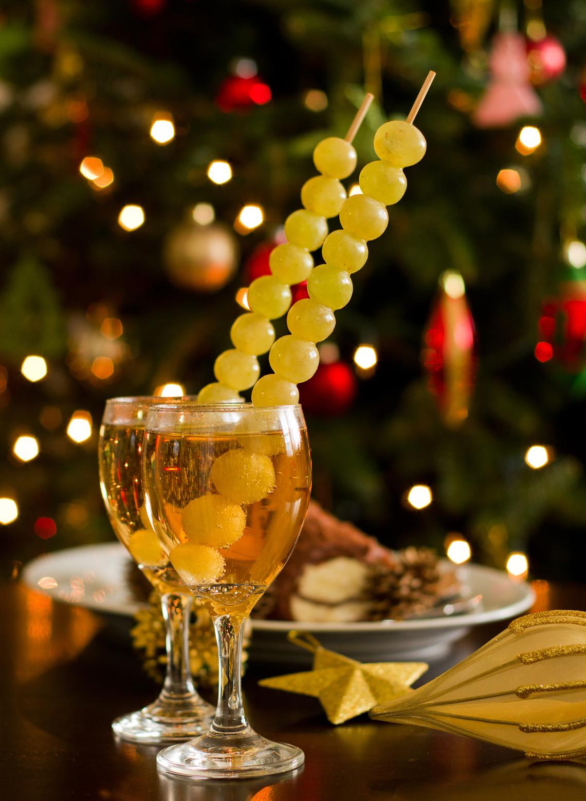 Copas de champaña con uvas verdes y decoración para la celebración de fin de año.