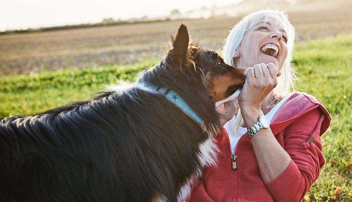Una mujer juega con su perro