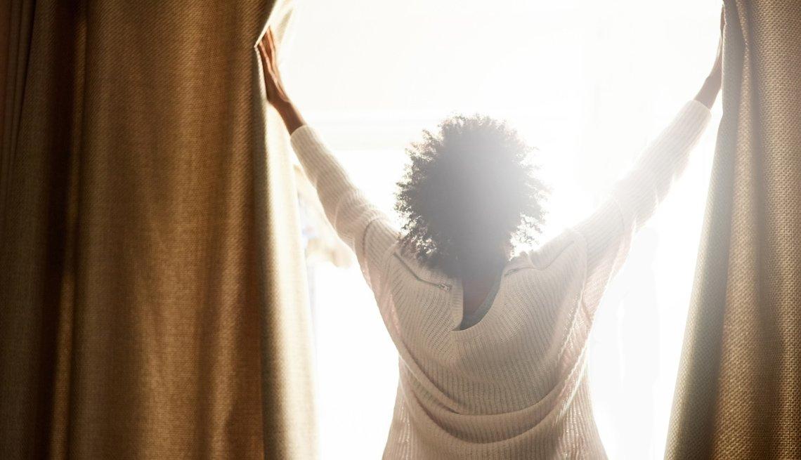 Mujer cierra la cortina de una casa