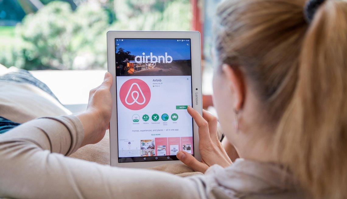 Mujer bajando la aplicación de Airbnb en una tableta electrónica