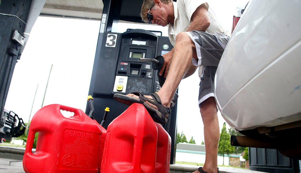 Un hombre en una estación de servicio llena tanques de combustible vacíos mientras se prepara para la llegada de un huracán