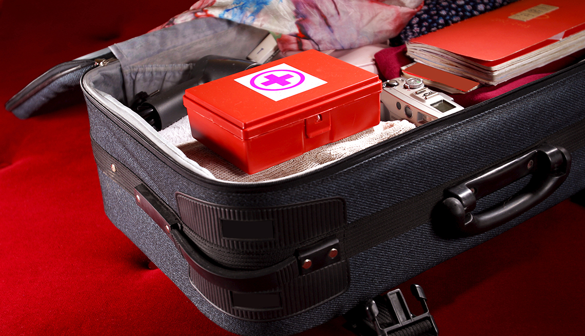 Una maleta está llena de artículos de emergencia como un botiquín de primeros auxilios, ropa, cámara y documentos