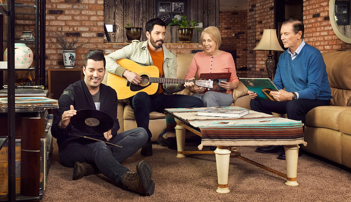 Jonathan and Drew Scott with their parents sitting around a table