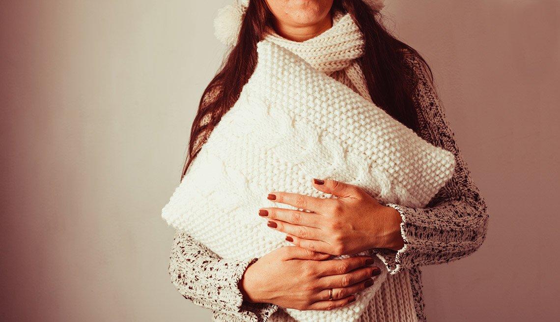 Mujer vestida con un saco de lana sostiene un cojín blanco tejido
