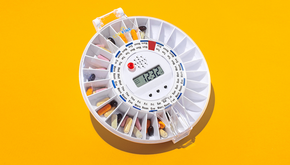 item 9 of Gallery image - round pill dispenser that shows three pill sorting compartments per day of the week plus a timer and printed times