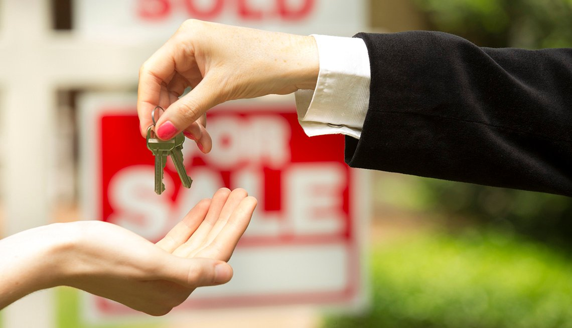Una persona entrega las llaves de una casa que se acaba de vender