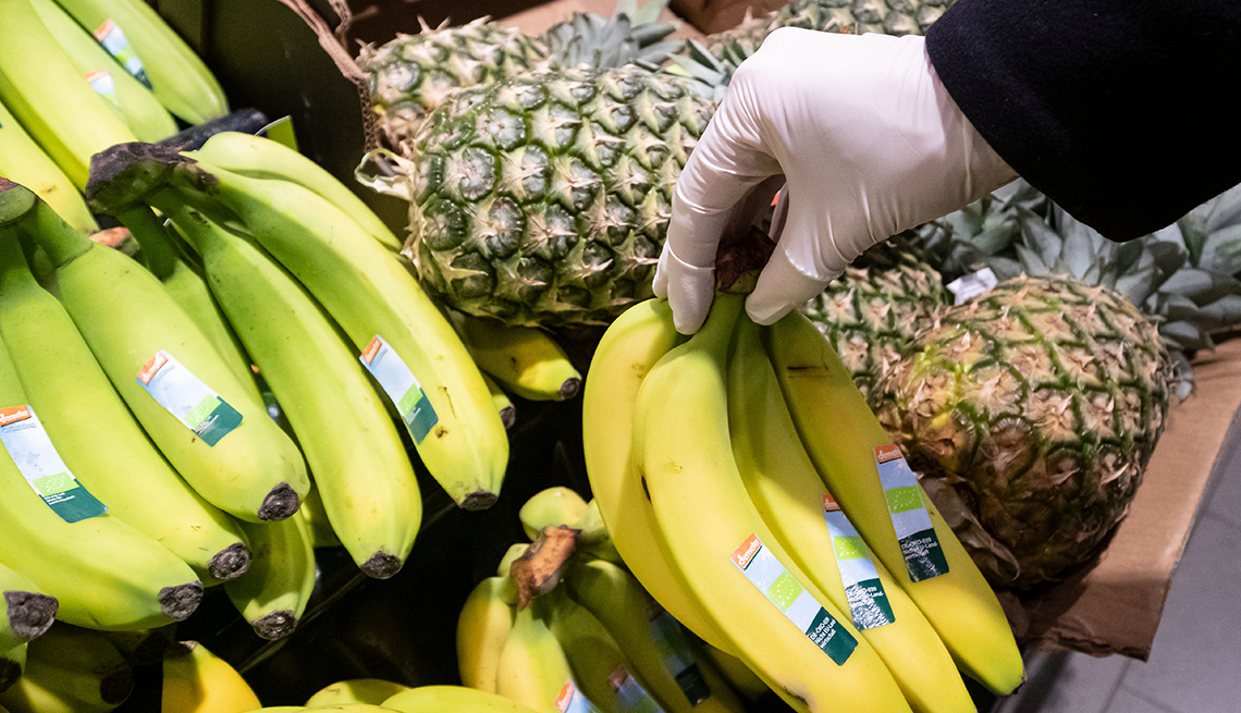 A woman with rubber gloves is shopping in an market.