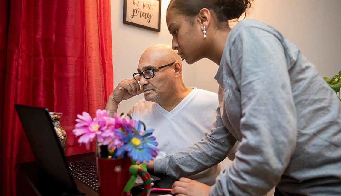 Niña ayuda a su abuelo a resolver un problema con la computadora