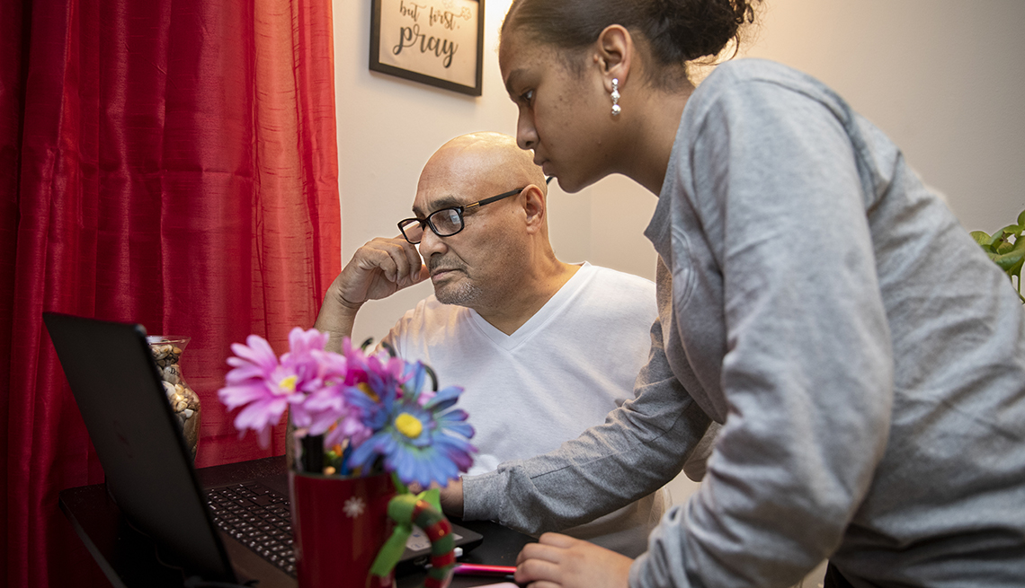 a teenage girl helps her grandfather on the computer in their home