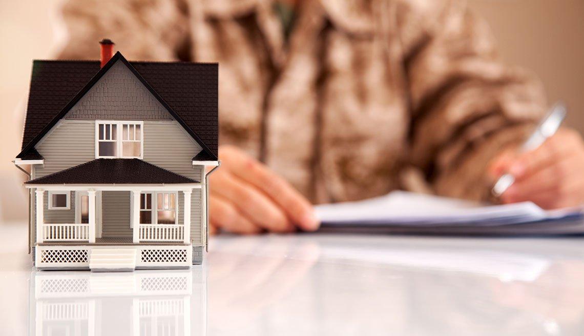 Hombre con uniforme de infantería de marina que llena documentos relacionados con bienes raíces