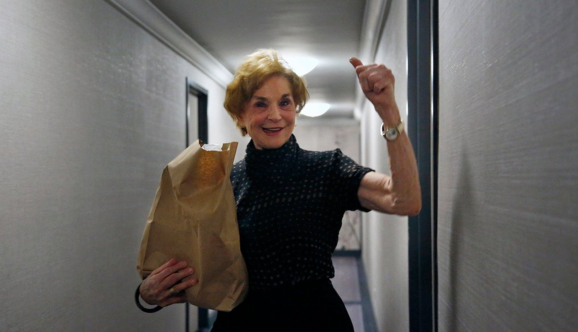 In this March 17, 2020, photo, Carol Sterling, 83, gives a thumbs-up to Liam Elkind after he delivers groceries to her apartment as part of a newly formed volunteer group he cofounded, Invisible Hands. The retired arts administrator has been sheltering at