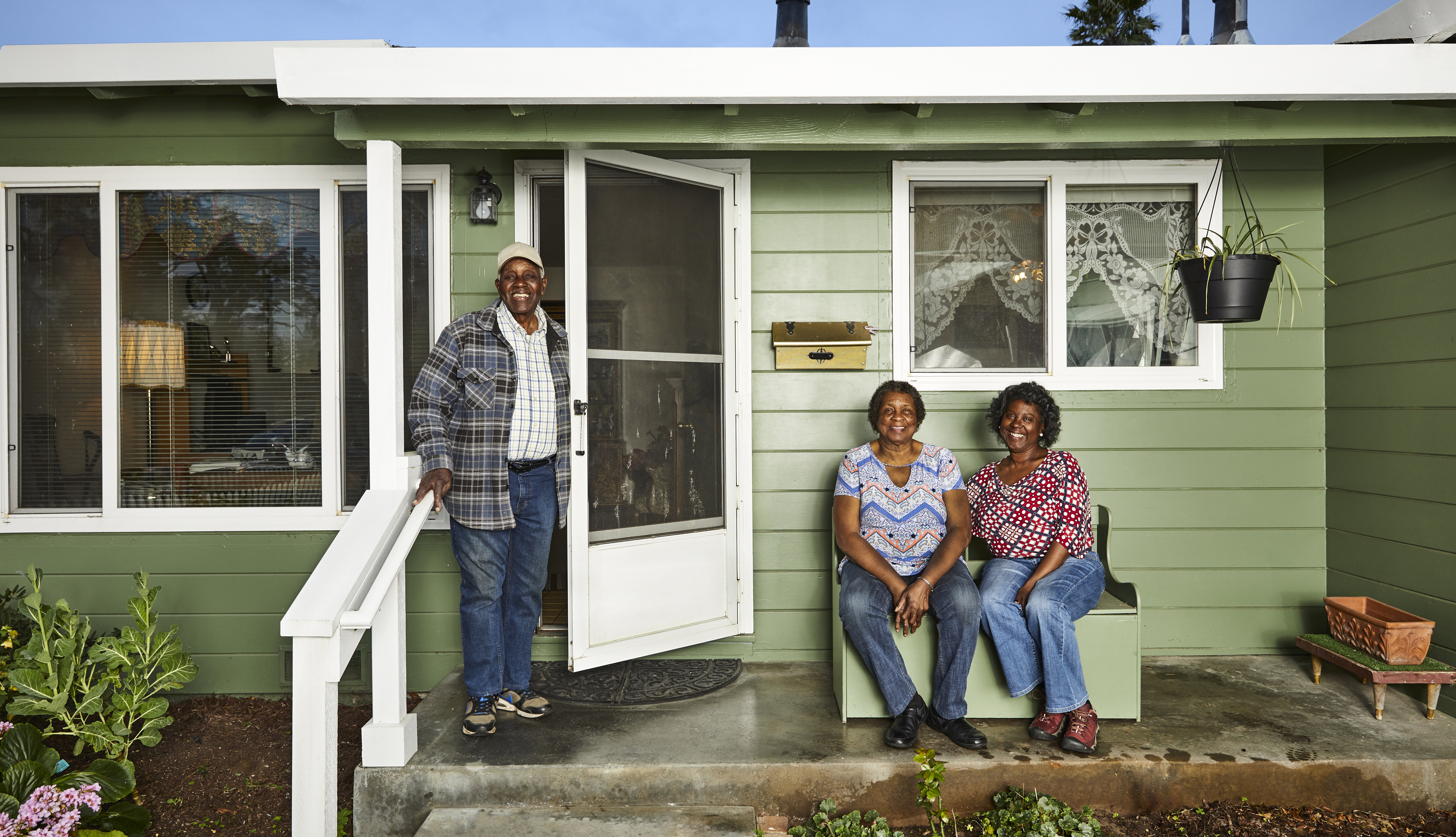 a smiling family on the porch of a green one level home