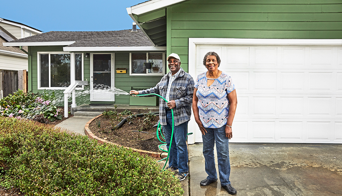 an older couple stands in the driveway of their home and the man holds a hose and is watering the front garden