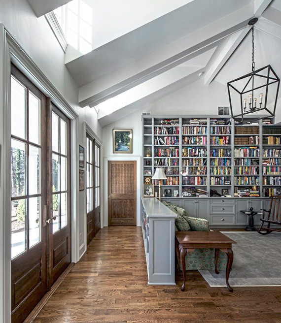 an interior of a home with high ceilings and skylights and a built in library
