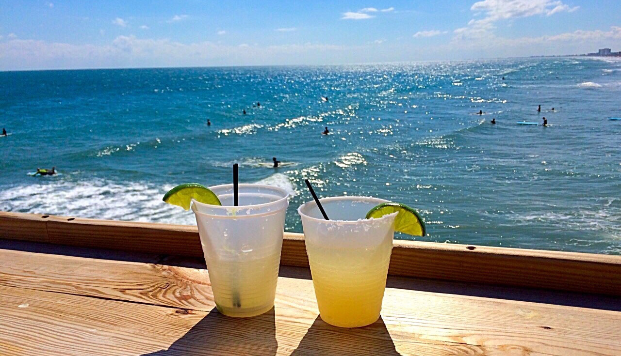 mixed drinks sitting on a wood bar overlooking the ocean on a bright summer day