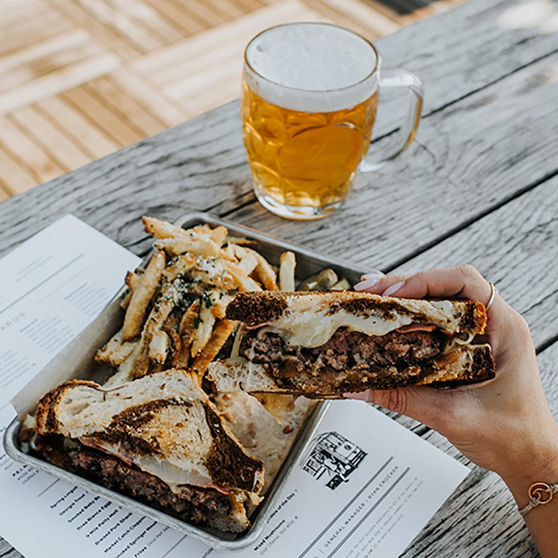 Sandwich con papas fritas y una cerveza en una mesa