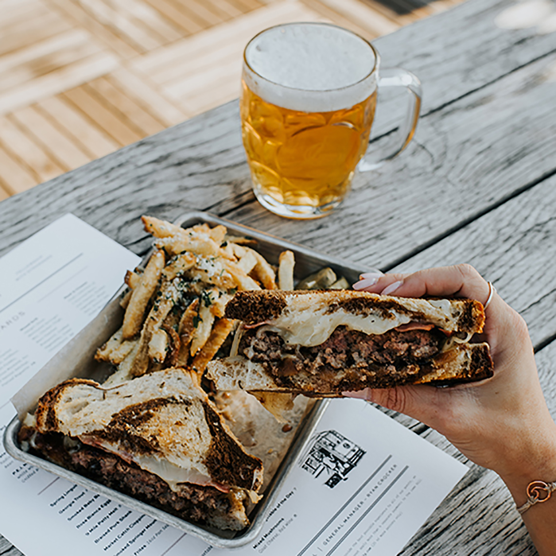 close up of a patty melt sandwich with french fries and a beer on a table