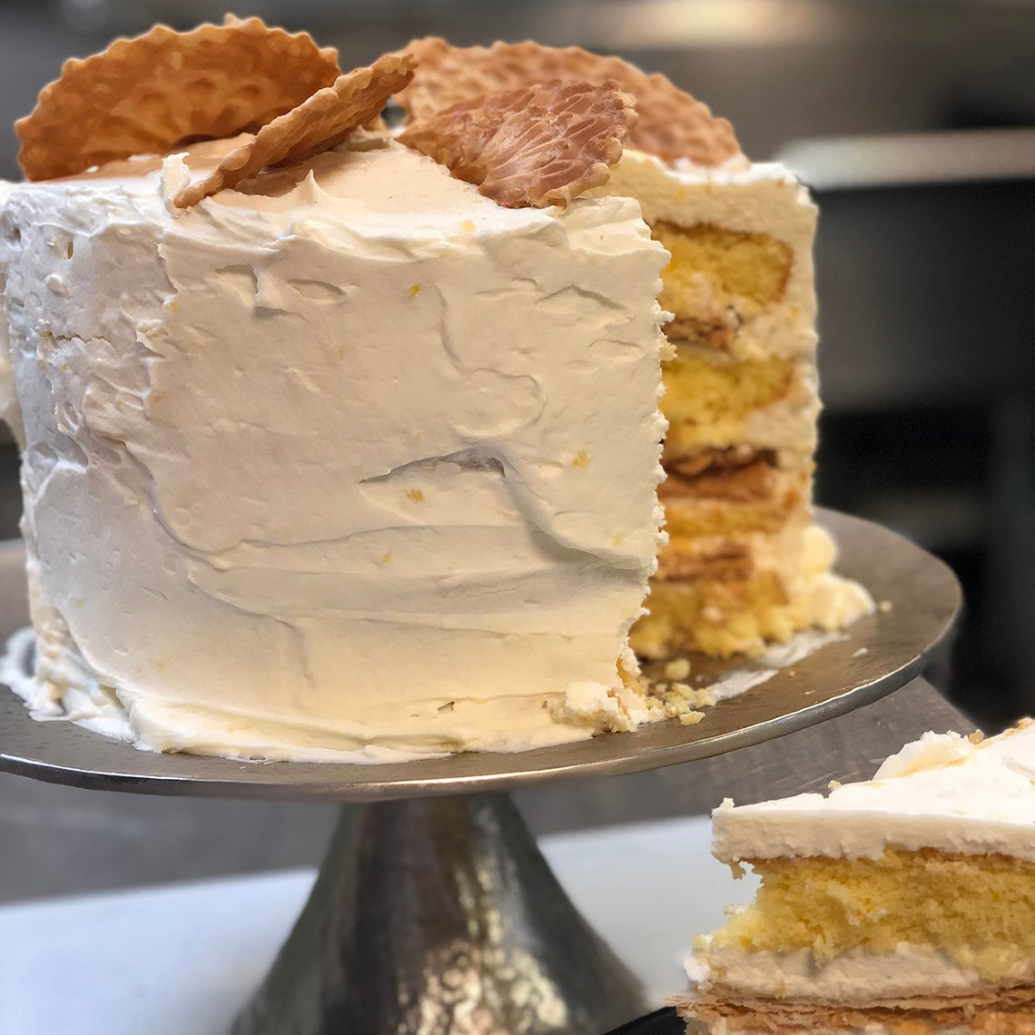 a yellow cake with white frosting on a serving platter
