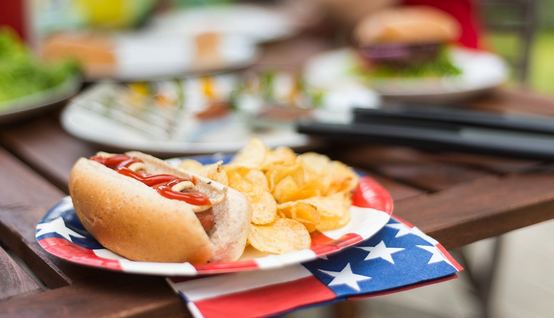 Hot Dog with potato chips at Fourth of July BBQ with people and other picnic items in the background. Influenced by the current trend in food photography of showing food in the foreground and lifestyle imagery out of focus in the background.