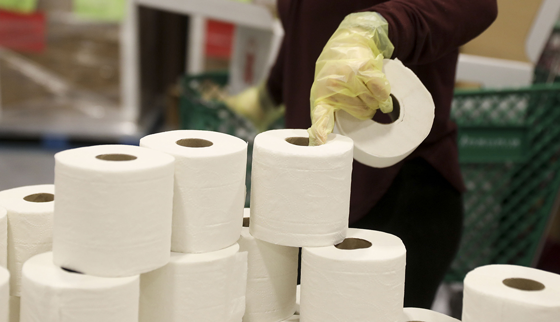 A volunteer picks up rolls of toilet paper at a Midwest Food Bank distribution warehouse in Normal, Illinois, U.S., on Wednesday, May 13, 2020. The coronavirus pandemic is forcing food banks across the country to find new ways to feed people  from slaught