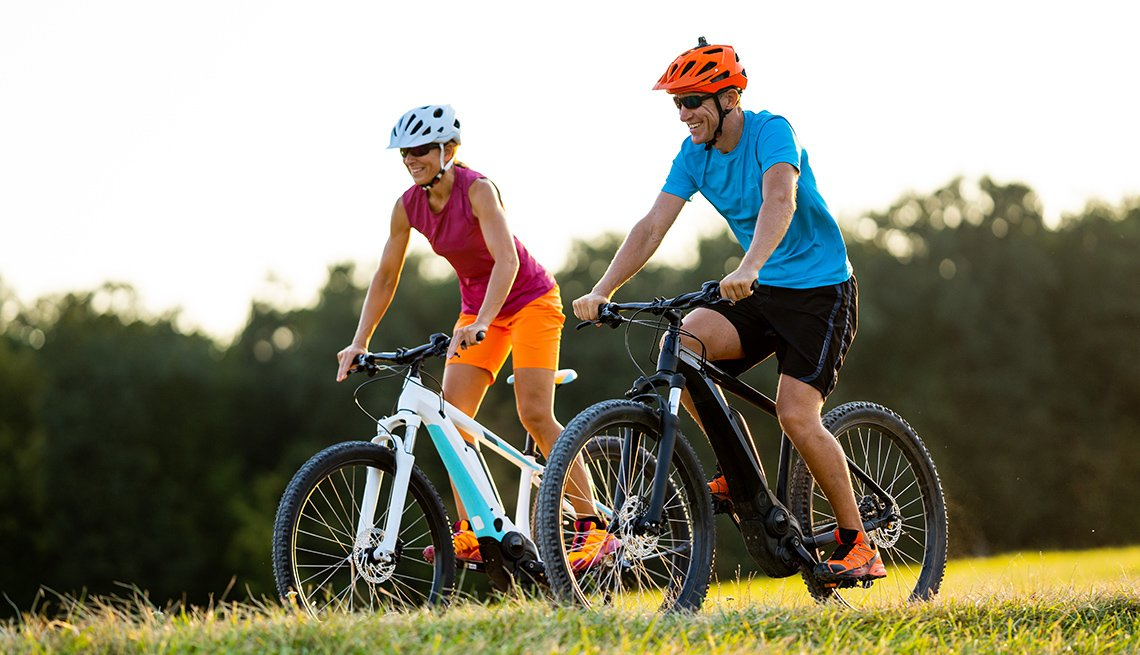 Smiling sporty fit couple enjoying summer cycling day outdoors in rural landscape on electric mountain bikes shallow focus on man